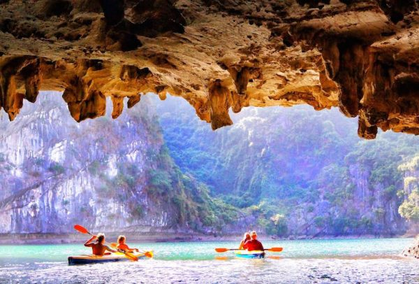 Tourists enjoy the kayaking experience through Luon Cave